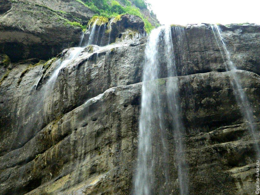 Красивая девушка позирует у искусственного водопада